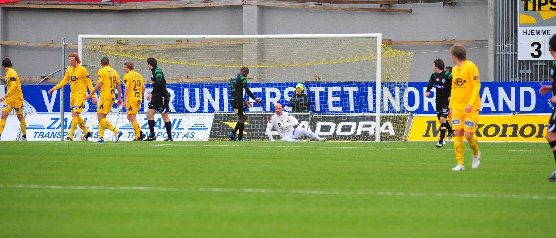 Bildet viser Jonas Kolstad som ligger på bakken med ballen i hendene, mens både gule glimtspillere og svarte løvhamspillere løper ut fra boksen mot midtstreken.