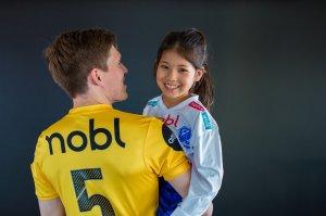 Nobl er stolt sponsor både i breddeklubben Junkeren og i Bodø/Glimt. A-lags-spiller Thomas Jacobsen, med Junkerenspiller Lisa Lewin på armen.