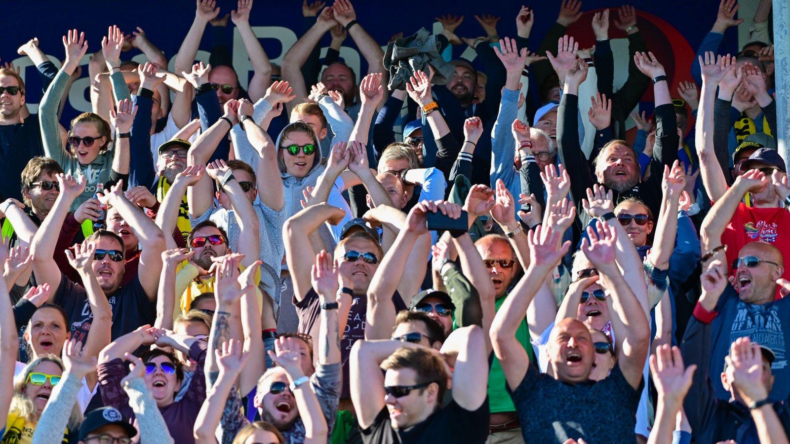 Publikum på Aspmyra tar bølgen for miljøet under kampen mot Strømsgodset.